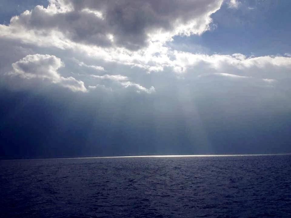 雨后初晴,阳光射穿云层,海面映起一道光幕,自是极